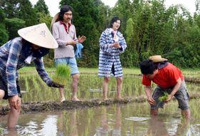 苗を植える外前田孝さん(右)の横で、「隼人田植え唄」を歌う片貝晴美さん(右から2人目)=曽於市大隅