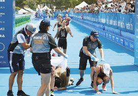 トライアスロンの東京五輪予選で、ゴール後に倒れ込む女子選手たち=8月、東京・お台場海浜公園で