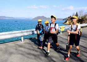 海沿いを元気いっぱいに歩く上浦小の児童