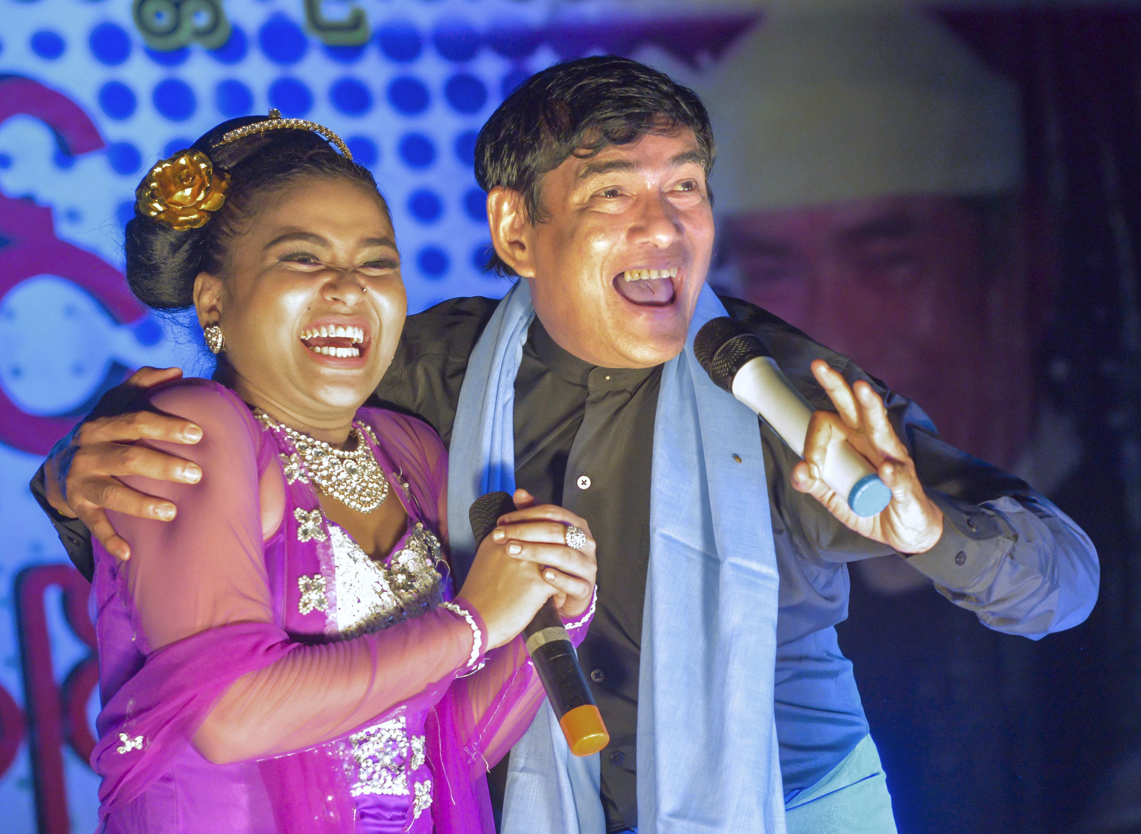 「アニェイン」の舞台に立ち、踊り子と歌うミャンマーの人気コメディアン、ミッター(右)。観客だけでなく共演者も即興で巻き込む。会場全体が大きな笑いで包まれた=ミャンマー・ダイウー(撮影・村山幸親、共同)