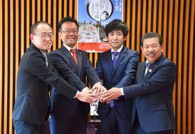 立地調印し握手する、砂川和雅社長(右から2人目)と読谷山洋司市長(同3人目)ら
