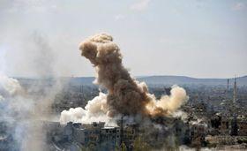 シリア・ダマスカス南部の「イスラム国」(IS)支配地域に対し、政権軍が行った空爆で上がった煙(国営シリア・アラブ通信提供・AP=共同)