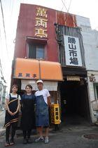 勝山市場で17年間営業し、今月で閉店する「萬両亭」と苑田さんら=長崎市勝山町