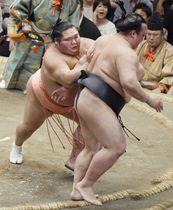 千代大龍(左)が押し出しで稀勢の里を破る=両国国技館