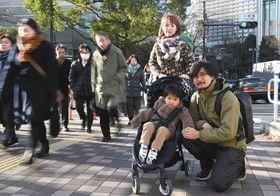子連れ通勤の大変さを訴える平本沙織さん(中央奥)と夫の知樹さん(右)、長男の律樹君=東京都品川区で