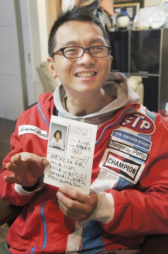 羽根田卓也選手からの手紙を手に笑顔の中西拓馬さん=2019年12月、名古屋市