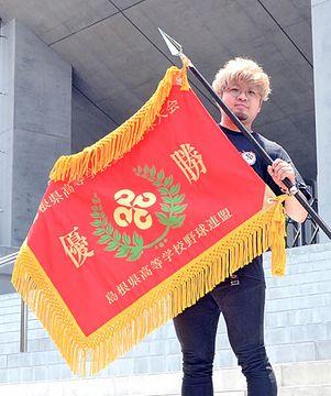 寄贈した優勝旗を手にする野田峻也さん=出雲市大社町北荒木、島根県立浜山球場