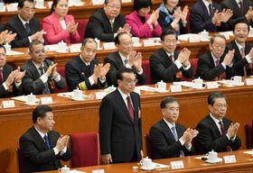 中国全人代の全体会議で再選され、拍手を受ける李克強首相(前列左から2人目)。左隣は習近平国家主席=18日、北京の人民大会堂(共同)