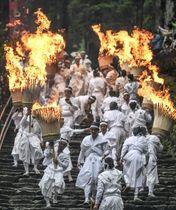 熊野那智大社の例大祭「那智の扇祭り(火祭)」で、燃えさかる大たいまつを担いで参道を練り歩く白装束の氏子ら=14日午後、和歌山県那智勝浦町