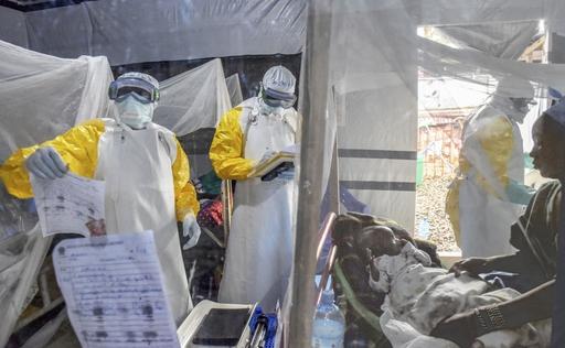 治療センターの隔離病室で、エボラ熱患者の赤ちゃんを診療する医師たち。免疫がある元患者の職員(右端)は防護服を着ないで赤ちゃんに直接触り世話をしている=19年9月、コンゴ・ベニ(共同)