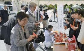 高野山の金剛峯寺前で熊本県西原村のスイカを参拝客に振る舞う高野山高校の女子生徒(右)=21日午後、和歌山県高野町