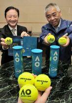テニス全豪オープンの公式球を持つ住友ゴム工業の旭野昌宏さん(左)と丹羽邦夫さん=神戸市中央区脇浜町3