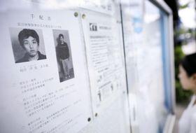 近鉄富田林駅近くの掲示板に張られた樋田淳也容疑者の顔写真入りのチラシ=14日午後