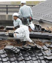 地震で被害を受けた屋根瓦を撤去する人たち=22日午前、山形県鶴岡市小岩川地区