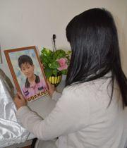 無くなった小関孝徳君の写真を見つめる母代里子さん=2月8日、埼玉県熊谷市