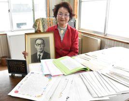 表彰を受けた子どもたちの手紙を並べ、設立者の椎屋さんの写真を手にする木村理事長