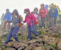 霧に覆われた磐梯山山頂を歩く登山者=28日午前