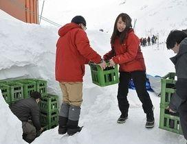 日本酒を雪の中に運び込む中央アルプス観光の社員ら