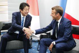 会談で握手するフランスのマクロン大統領(右)と安倍首相=24日、フランス南西部のビアリッツ(共同)