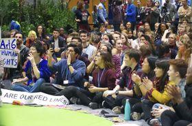 COP25の会場で座り込み、地球温暖化対策強化を訴える若者ら=13日、マドリード(共同)