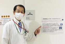 透析施設の更衣室に張った感染防止の注意書きを指す東京都済生会中央病院の竜崎崇和副院長=2020年5月、東京都港区(同病院提供)