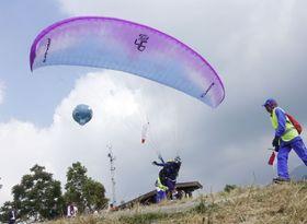 パラグライディング競技で滑空のため助走する選手=インドネシア・ボゴール(共同)