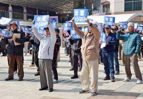 シュプレヒコールを上げる参加者=鹿児島市のJR鹿児島中央駅前広場