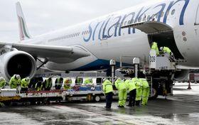 成田空港に帰国した、スリランカの連続爆破テロで亡くなった高橋香さんの遺体が納められたひつぎ(中央)=25日午前7時35分
