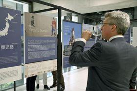 20日、ロンドンのカムデン区役所で始まった鹿児島展で、焼酎を飲みながらパネル展示を見る男性(共同)