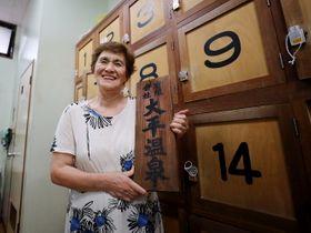 「大平温泉」の看板を持つ百枝さん。「100年間、利用してくれた皆さんにありがとうと言いたい」=長崎市曙町、大平湯
