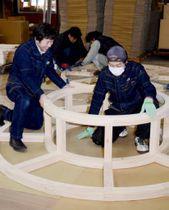 円形のジャングルジムを組み立てる土井木工の従業員