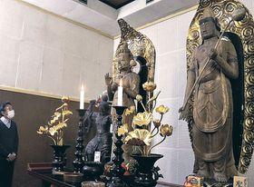 常楽寺の重文の観音像に見入る参拝者=富山市婦中町千里