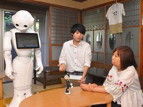 人型ロボット「ペッパー」の横で、見学者にプログラミング教育の内容を説明する吉田右京さん=羽島郡笠松町春日町、アプリ食堂