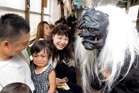 近づいてきた妖怪におびえる子どもと、その様子を楽しむ大人たち(京都市内・京福電鉄嵐山線)