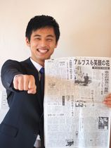 甲子園での応援を報じる5年前の新聞記事と同じ演舞ポーズをして、後輩たちにエールを送る細田悠太さん