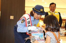 【啓発品を配り、交通安全を呼び掛ける武田さん(左)=東員町長深のイオンモール東員で】