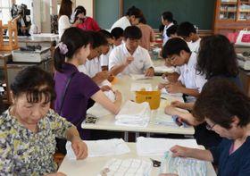 協力して雑巾を作る生徒と地域住民