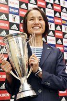 ヨルダンから帰国し、優勝杯を手に笑顔を見せる「なでしこジャパン」の高倉麻子監督=22日夜、成田空港