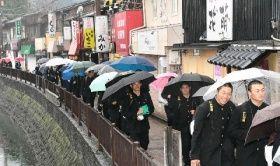 甲子園に向け、堀川沿いの飲食店街を歩きJR折尾駅へ向かう東筑の選手たち