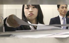 上場企業の2018年9月中間決算発表がピークを迎え、報道機関向けに資料を投函する担当者=9日午後、東京・日本橋兜町の東京証券取引所