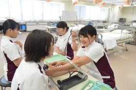 「仲間と励まし合いながら勉強に取り組んでます」と実習に臨む蛯名綾香さん(右)=8月2日、八戸学院大