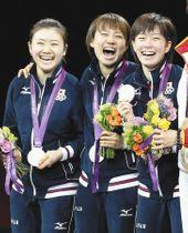 2012年8月7日、ロンドン五輪卓球女子団体、銀メダルを手に表彰台で笑顔を見せる(左から)福原、平野、石川=沢田将人撮影