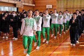 全校生徒の拍手に迎えられ、壮行会に臨む藤山主将(中央)ら選手たち=松浦高体育館