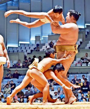 「ちびっこ相撲」で力士に挑戦する子どもたち=16日、宜野湾市・沖縄コンベンションセンター(金城健太撮影)