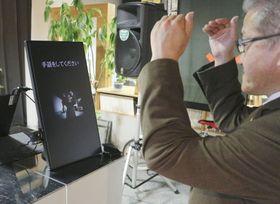 AIを活用した手話通訳を実演する開発報告会の参加者=31日午後、札幌市