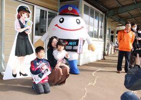 「西浦ありさ」の等身大パネルを前に記念撮影をする親子連れ=平戸市田平町