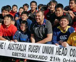 中学生たちと記念撮影するオーストラリア代表のチェイカヘッドコーチ(中央)
