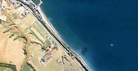 北海道・猿払村の沿岸を撮影した航空写真。旗マークの場所が「エサンベ鼻北小島」があるとされる場所(国土地理院ウェブサイトより)