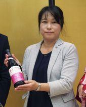 「極上の甘口」を手にする大関の笹倉哲子海外営業部長=25日、北京(共同)