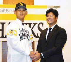 仮契約を結び、山本省吾スカウト(右)と握手する泉圭輔投手=金沢市内で